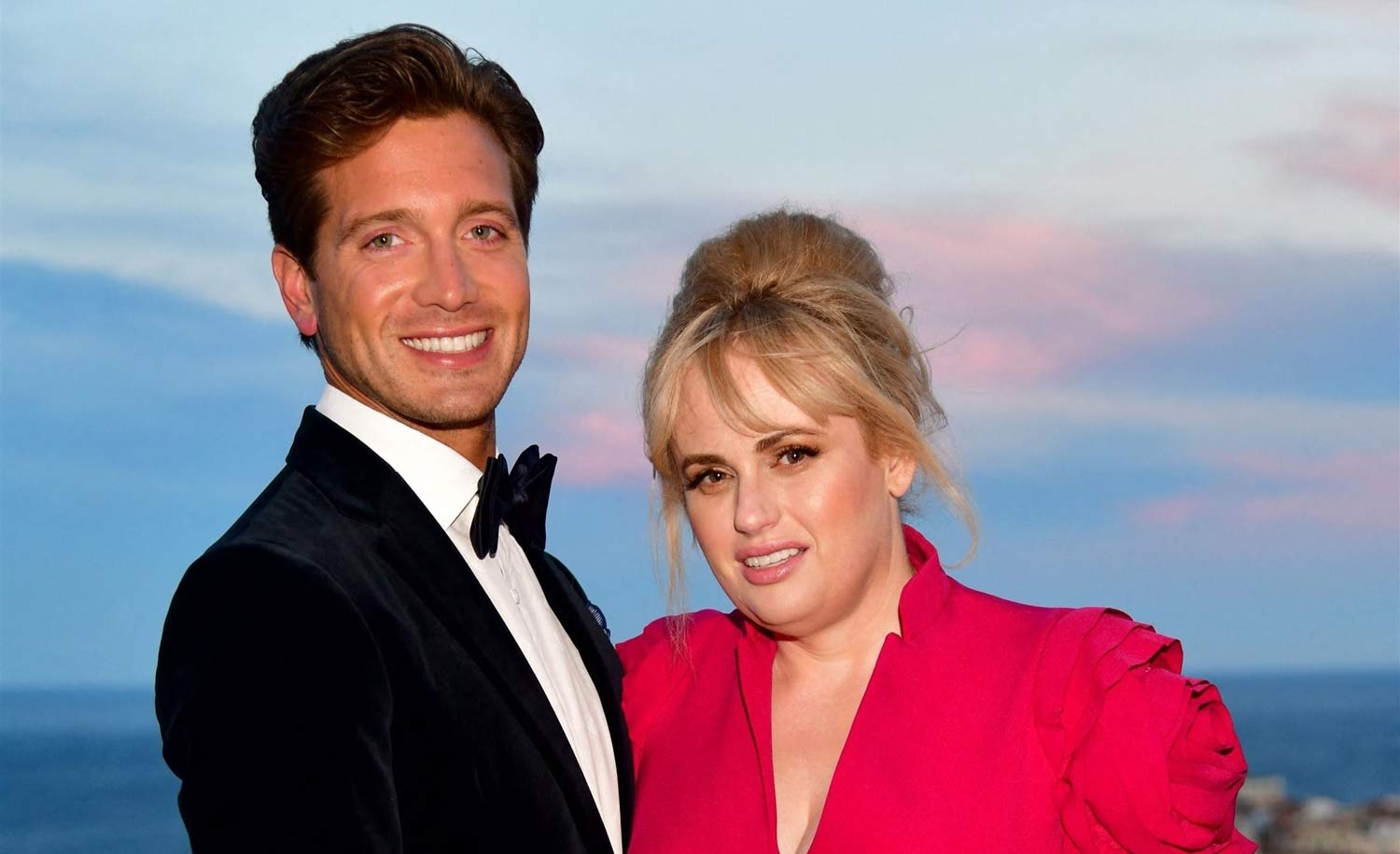 Rebel Wilson And Her BF Jacob Busch Pack The PDA In Cute Beach Video – Check Out Her Stunning Strapless Bathing Suit!